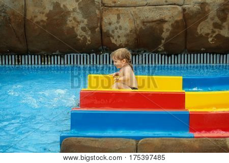 Cute baby boy with blond hair sliding from colorful waterslide in blue water or aqua park outdoors on sunny summer day on wet grey stone background