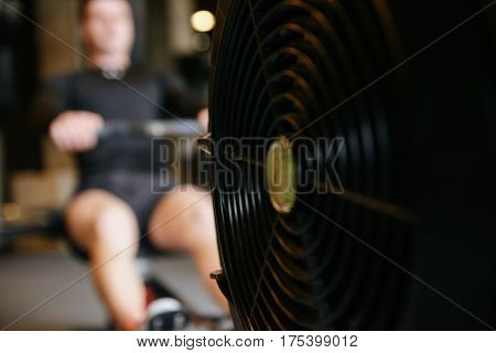 Muscular man which using rowing machine in gym. Focus on the rowing machine