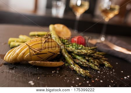 Grilled green asparagus with ingredients on a slate plate in a restaurant