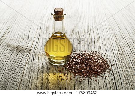 Linseed oil with seeds on wooden background
