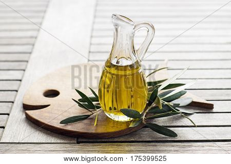 Olive oil with branch on the wooden table