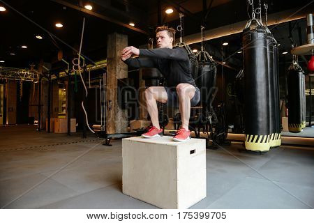 Athletic man which jumping on box in gym