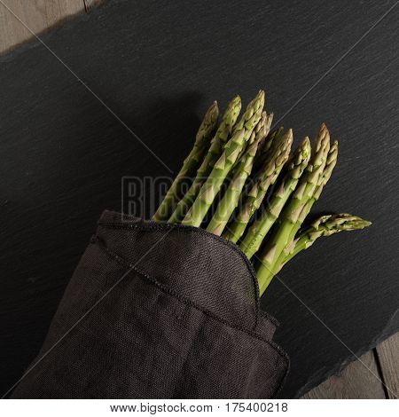 Fresh green asparagus on a elegant black slate plate