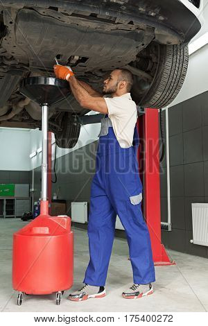 Mechanic Draining the Oil of a Car in an Oil Drain Tank