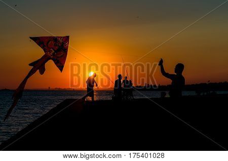 Silhouettes Of Father And Son Flying A Kite In Sunset