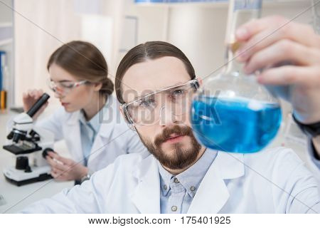 Pensive male scientist holding flask with chemical reagent
