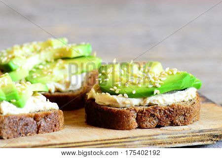 Open avocado and hummus sandwiches with sesame on a wooden board. Healthy vegan sandwiches. Closeup