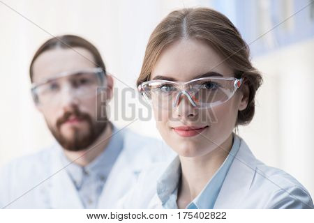 Portrait of young professional scientists in protective eyewear looking at camera