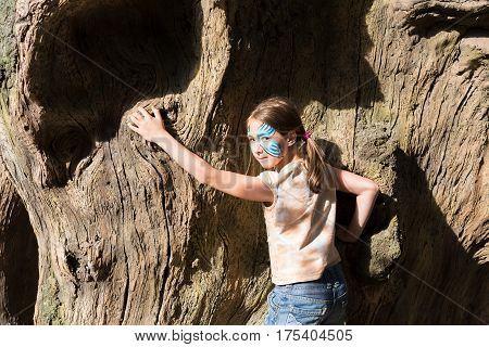 Small girl full-length portrait with funny face art painting. Female child climb big old tree with blue butterfly drawing on her face. Children event, birthday party and creative entertainment.