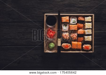 Japanese food restaurant take away, sushi maki gunkan roll plate or platter set. Chopsticks, ginger, soy sauce, wasabi. Meals at rustic wood background, craft delivery box. Top view.