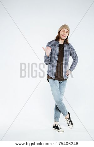 Vertical image of hipster which pointing away and looking at camera. Full length portrait
