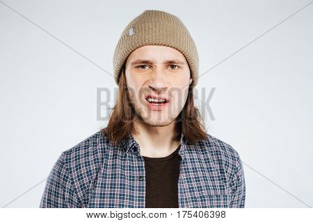 Close up portrait of displeased hipster in shirt and hat which looking at camera. Isolated gray background