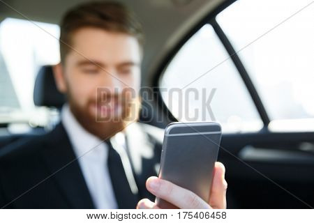 Smiling bearded business man in suit looking at mobile phone in his hand while sitting in the back seat of a car. focus on mobile phone