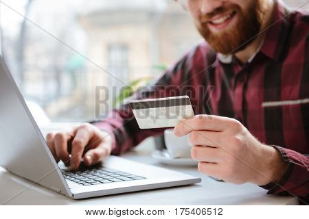 Cropped picture of cheerful bearded young man sitting in cafe while using laptop computer and holding debit card.