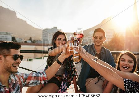 Friends having fun and drinking outdoor on a rooftop get together. Group of friends hanging out and toasting drinks outdoors. poster