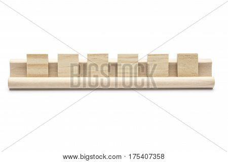 Six blank wooden tiles on a rack isolated on white background.