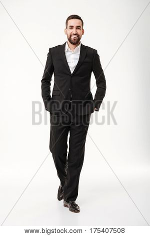 Full lenght photo of cheerful young businessman standing and posing over white background. Looking at camera.