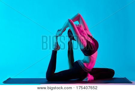 one caucasian woman exercising  Rajakapotasana  King pigeon yoga exercices  in silhouette studio isolated on blue background