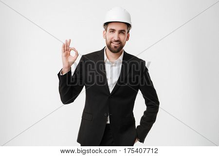 Picture of young attractive architect wearing helmet over white background make okay gesture.