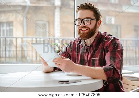 Picture of happy bearded young man student wearing glasses sitting in cafe while using tablet computer. Looking aside.