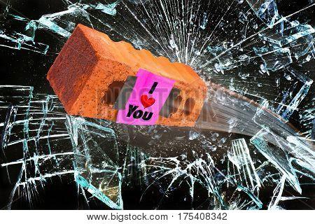 I love you brick going through glass window.