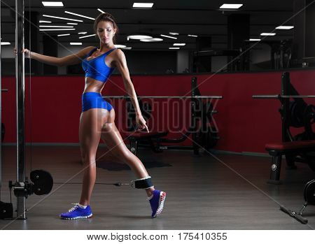 Beautiful slender brunette girl in blue sportswear doing exercises in the gym. Concept of sport and a healthy lifestyle, diet.