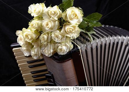 Vintage accordion and a bouquet of white roses. Concept of a nostalgic music. Still life with a traditional folk musical instrument.