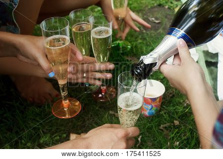 Hands Of Woman Holding Colorful Glasses And Pouring Champagne At Joyful Party In Summer Park, Bridal