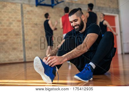 Handsome basketball player tying a shoe and getting ready for the game.