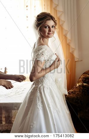 Luxury Gorgeous Blonde Bride Getting Dressed In The Morning With Helping Bridesmaids In Bright Room