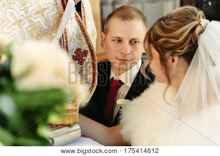 Wedding Ceremony Of Happy Elegant Blonde Bride And Stylish Groom, Holding Hands On Bible And Taking