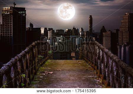 Old concrete bridge with wooden across to skyscrapers with super moon background at night. Dark tone and high contrast style. Vintage tone. The moon were NOT furnished by NASA.