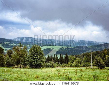 Dramatic cloudy misty landscape. mountain meadow and forests, both deciduous broadleaved and needle coniferous trees, electric overhead power line and horizon covered in clouds and mist, Czech republic, central Europe, Orlicke hory