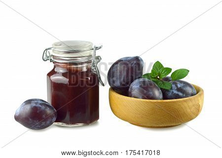Plum jam in the jar and fresh plums in wooden bowl