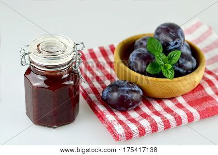 Homemade plum jam in the jar and fresh plums in wooden bowl