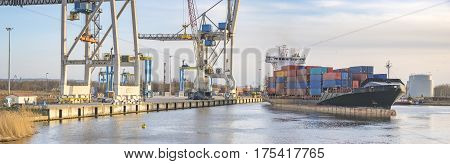 sea container flows into port for unloading harbor cranes and gantries