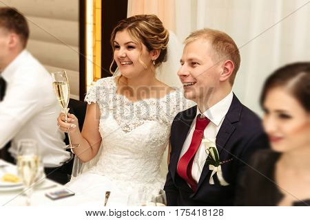 Happy Gorgeous Bride And Stylish Groom Cheering And Toasting With Guests And Family At Luxury Weddin