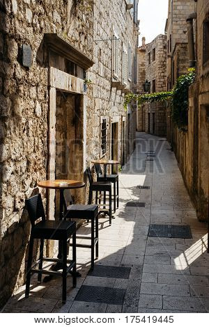 Chair and table of the restaurant on a narrow European street in the historic city.