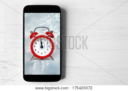 Midnight countdown concept: Mobile phone with vintage clock on the screen showing midnight