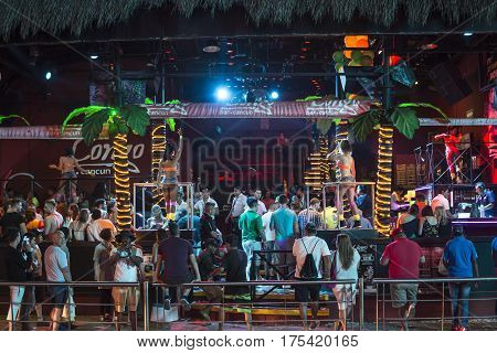 CANCUN MEXICO - MARCH 1 2017: Spring breakers celebrate in a popular Cancun nightclub with a tropical interior and go-go dancers while spectators observe from outside.