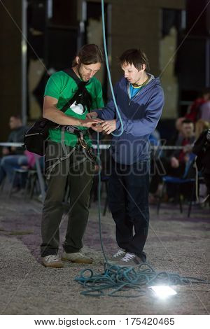 Rock Climbers arranging belay with rope and devices in night spot light at National Climbing Championship, Dnipro, Ukraine, May 21, 2016