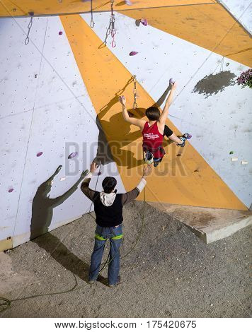 Elegant female Climber starting her Try on climbing wall. Belaying Referee opens Hands to protect her. National Climbing Championship, Lead Finals, Dnipro, Ukraine, May 21, 2016