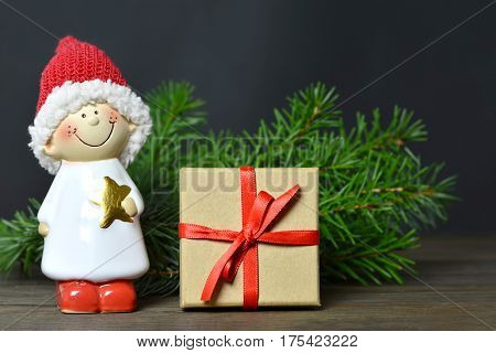 Christmas gift and Santa's helper on dark wooden background