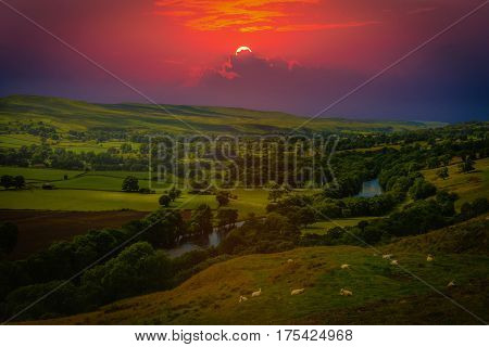 Sunset over mountains and meandering River making its way through lush green rural farmland in England.