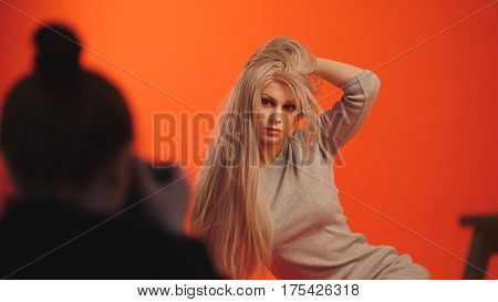Backstage: blonde female model posing for photographer in red studio, close up