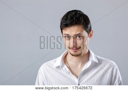 handsome young frustrated and resentful brunette man in white shirt on gray background.