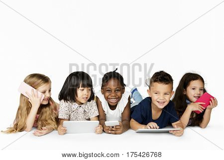 Happiness group of cute and adorable children lay down and using digital devices