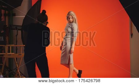 Blonde girl posing for photographer - model stands near red background, telephoto