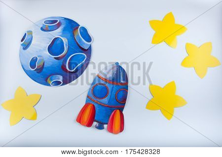 Space picture painted by gouache. Blue planet rocket and yellow stars on white background