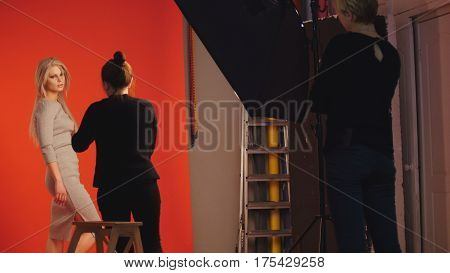 Photo backstage: blonde girl model plays long hair - photographer take a picture in studio, red background